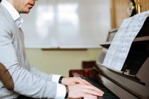 Handsome man playing piano during rehearsal in recording studio. — Stock Photo