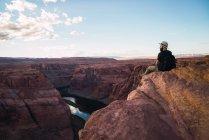 Vue arrière du gars barbu avec sac à dos regardant le beau canyon et la rivière calme par une journée ensoleillée sur la côte ouest des États-Unis — Photo de stock