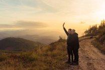 Vista lateral do casal homossexual abraçando na rota na escuridão e vista pitoresca do vale no nevoeiro — Fotografia de Stock