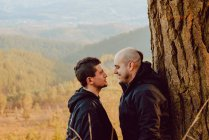 Vista laterale di allegra coppia omosessuale che si guarda vicino all'albero nella foresta e pittoresca vista sulla valle — Foto stock