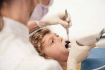 Donna in maschera e uniforme medico fare la scansione dei denti del bambino mentre si lavora in clinica dentista — Foto stock