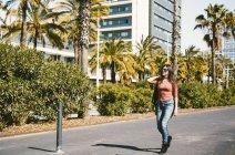 Ragazza adolescente che cammina felicemente per le strade della città in una giornata di sole — Foto stock