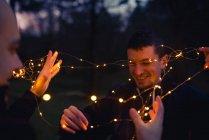 Nahaufnahme von Männern beim Entwirren beleuchteter Lichter im dunklen Wald am Abend auf verschwommenem Hintergrund — Stockfoto