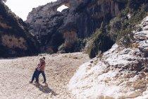 Pareja joven abrazándose en el cañón entre montañas rocosas en un día soleado - foto de stock
