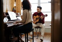 Погляд на молоду чорну жінку, що грає на піаніно поруч з чоловіком у музичній студії — стокове фото