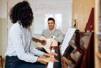 Seitenansicht einer jungen schwarzen Frau, die im Musikstudio neben einem Mann Klavier spielt und Gitarre spielt — Stockfoto