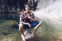 Happy adult woman sitting on rock in tranquil transparent water of lake enjoying nature and smiling away — Stock Photo