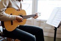 Donna nera che suona la chitarra durante le prove in studio di registrazione — Foto stock