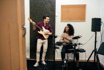 Homem alegre tocando guitarra e mulher tocando bateria — Fotografia de Stock