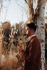 Jeune musicien jouant le saxophone au coucher du soleil au lac — Photo de stock