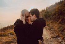 Vista laterale della coppia omosessuale che si abbraccia sul sentiero nella foresta nella giornata di sole — Foto stock