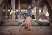 Shirtless man dancing on sand in weathered building — Stock Photo