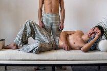 Stilvolle hemdlose homosexuelle Paare Modelle posieren und legen sich in eine gepolsterte moderne Bank — Stockfoto