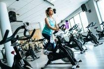 Mulher com toalha e água na máquina de exercício — Fotografia de Stock