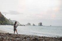 Mujer con cámara caminando en la costa del mar - foto de stock
