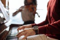 Вид сбоку на молодого человека, играющего на фортепиано рядом с черной женщиной, играющей на скрипке в музыкальной студии — стоковое фото