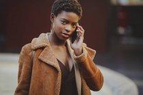 Afro-americano elegante donna parlando sul cellulare e guardando la fotocamera sulla strada — Foto stock