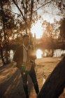 Молодий романтичний музикант грає на саксофоні в парку біля води в сонячний день — стокове фото