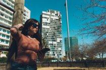 Adolescente olhando para o smartphone na rua em um dia ensolarado — Fotografia de Stock