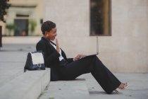 Sorrindo confiante afro-americano mulher elegante em traje navegando no laptop e sentado em escadas perto do saco na rua — Fotografia de Stock