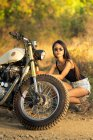 Stylish young asian woman in sunglasses fixing motorbike in countryside — Stock Photo