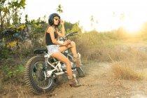 Привлекательная молодая женщина в шортах и туфлях на высоком каблуке опирается на мотоцикл в сельской местности — стоковое фото