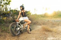 Attractive young woman in shorts and high-heeled boots leaning on motorbike in countryside — Stock Photo