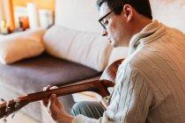 Nahaufnahme eines Mannes in Pullover und Brille, der zu Hause Gitarre spielt — Stockfoto