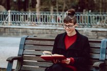Young smiling elegant woman in eyeglasses reading book and sitting on bench in city park — Stock Photo