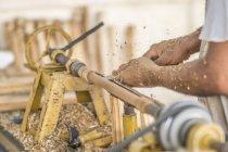 Close-up de mãos masculinas fazendo detalhes e usando máquina de trabalhar madeira no local de trabalho — Fotografia de Stock