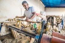 Человек с помощью деревообрабатывающей машины на рабочем месте — стоковое фото