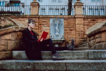 Young elegant woman in eyeglasses reading book and sitting on stairs in front of building in city — Stock Photo