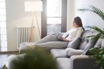 Mujer joven sonriente usando portátil y descansando en el sofá en casa - foto de stock