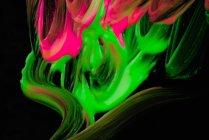 Derrames de pigmento grueso de varios colores mezclando sobre fondo negro - foto de stock