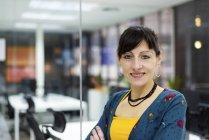 Портрет улыбающейся женщины-менеджера, стоящей у стеклянной стены в современном офисе — стоковое фото