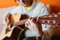 Close-up of man playing guitar on orange background — Stock Photo