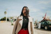 Задумчивая молодая женщина в модном наряде с курткой, стоящей на размытом фоне пляжной парковки — стоковое фото