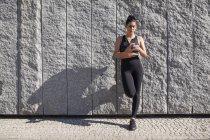 Femme brune appuyé contre le mur de granit tout en utilisant le téléphone — Photo de stock
