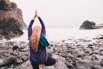 Young woman with upped hands meditating and standing on one leg on rocks on sea coast — Stock Photo