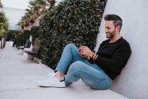 Bel homme élégant et heureux en tenue décontractée utilisant un téléphone portable et assis près d'un mur gris — Photo de stock