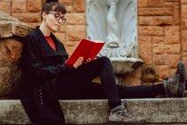 Giovane donna elegante in occhiali libro di lettura e seduta sulle scale — Foto stock