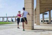 Couple in sportswear stretching before running near architecture with columns in city — Stock Photo