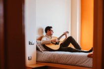 Man playing guitar on bed at home — Stock Photo