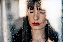 Attractive female with red lips with closed eyes behind transparent glass — Stock Photo