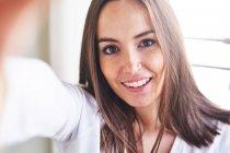 Ritratto di giovane donna felice davanti alla finestra — Foto stock