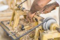 Крупный план мужских рук, делающих детали и использующих деревообрабатывающую машину на рабочем месте — стоковое фото