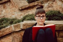 Giovane donna elegante in occhiali appoggiata sul muro di pietra con libro e guardando la fotocamera — Foto stock