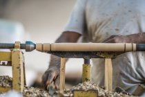 Primer plano de las manos masculinas haciendo detalle y utilizando la máquina de carpintería en el lugar de trabajo - foto de stock