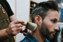 Seitenansicht des Friseurs mit Pinsel in der Nähe glücklich gut aussehende stilvolle Mann sitzt im Stuhl im Salon — Stockfoto