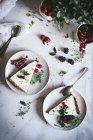Morceaux de tarte au citron vert avec des baies fraîches sur des assiettes en marbre blanc — Photo de stock